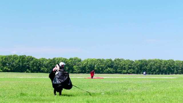 skydiver lands on the field and collects a parachute. - landing touching down stock videos & royalty-free footage