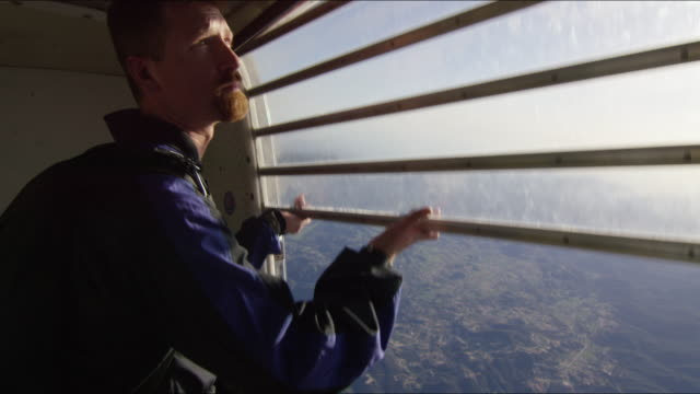 Skydiver opens airplane door and looks out