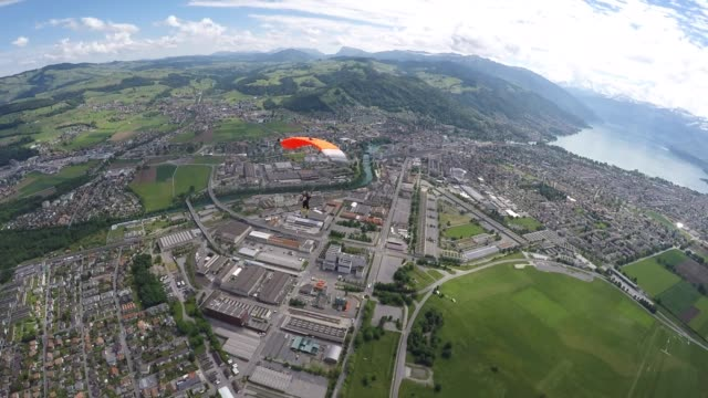 vídeos de stock e filmes b-roll de skydiver parachutes above swiss mountains and farmland - descer