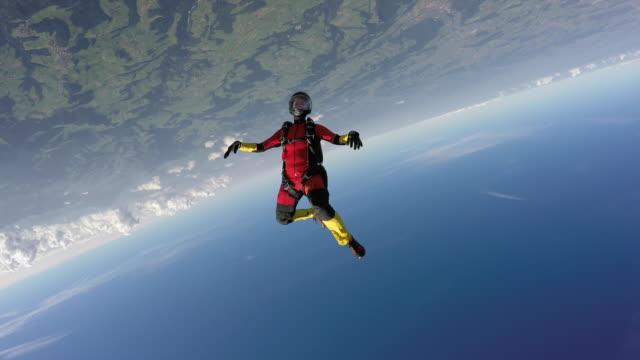 vidéos et rushes de skydiver performing acrobatics in free fall over alps - alpes suisses