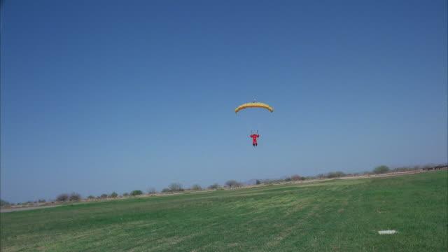 vidéos et rushes de a skydiver swoops past the camera, inches away. - un seul homme d'âge moyen