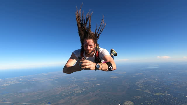 skydiver texting and distracted on his phone - skydiving stock videos & royalty-free footage