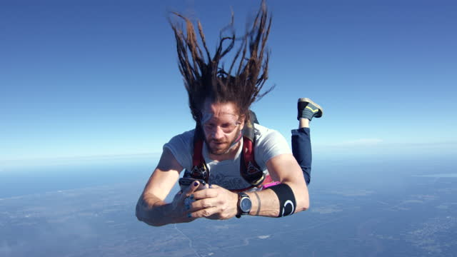 vidéos et rushes de skydiver texting and distracted on his phone - photophone