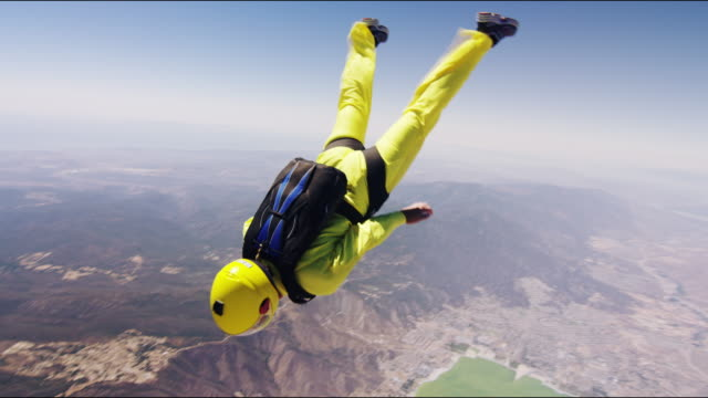 skydiver turns then passes camera - parachuting stock videos & royalty-free footage