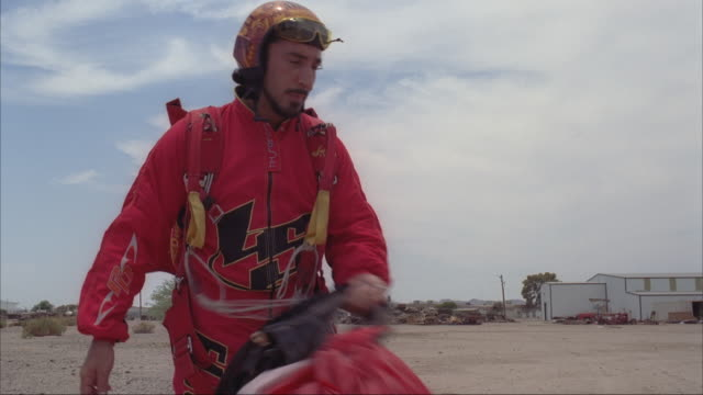 a skydiver walks off the landing area with his gear over his shoulder. - パラシュート点の映像素材/bロール