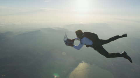 skydiver with laptop at sunset - herausforderung stock-videos und b-roll-filmmaterial