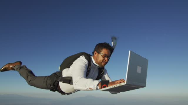stockvideo's en b-roll-footage met skydiver with laptop at sunset - humour