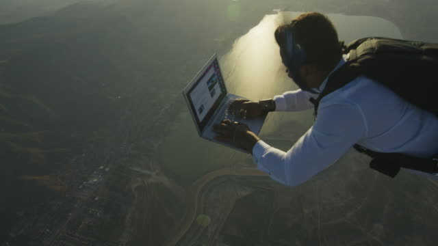 skydiver with laptop at sunset - positive emotion stock videos & royalty-free footage