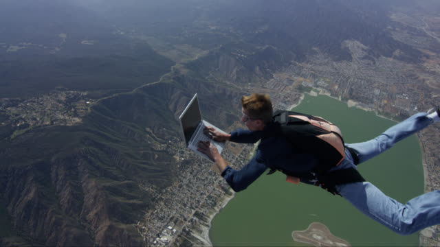 vídeos de stock e filmes b-roll de skydiver working on a laptop in free fall - eficiência