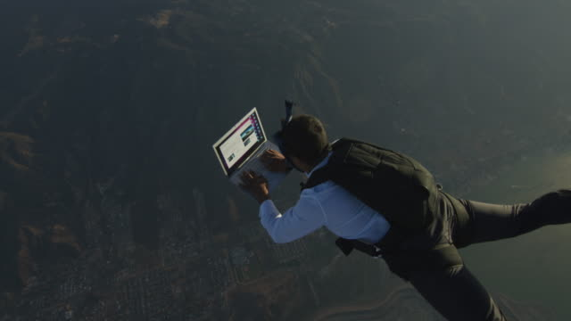 skydiver working on laptop in free fall at sunset - vederkvickelse bildbanksvideor och videomaterial från bakom kulisserna