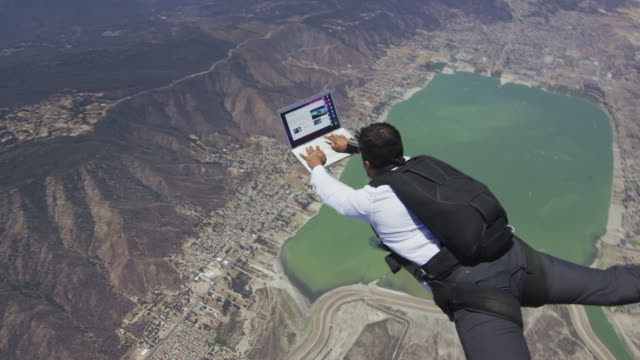 skydiver working on laptop in free fall - motivation stock-videos und b-roll-filmmaterial