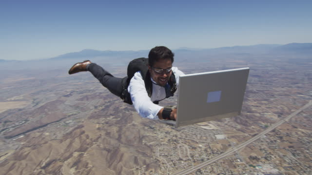 stockvideo's en b-roll-footage met skydiver working on laptop in free fall - pret