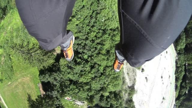vidéos et rushes de pov de pieds de parachutiste au-dessus des montagnes et à l'atterrissage - parachute