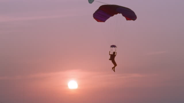 skydivers glide down over a lake and land. - 1994 stock-videos und b-roll-filmmaterial