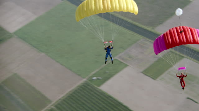 skydivers glide over the countryside. - parachute stock videos & royalty-free footage