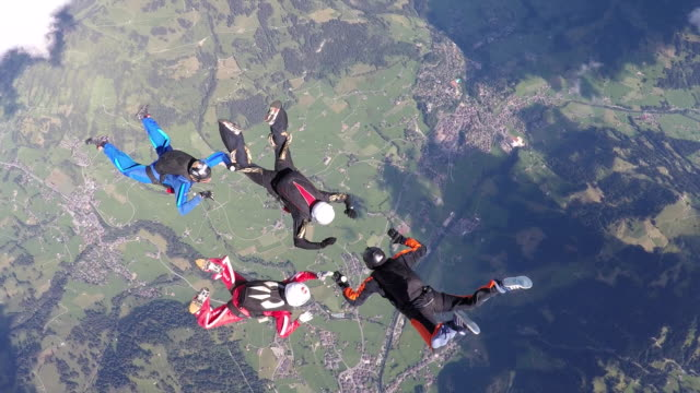 skydivers hold hands in freefall - four people stock videos & royalty-free footage