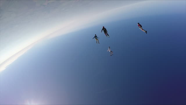 Skydivers jump from helicopter, perform aerial acrobatics