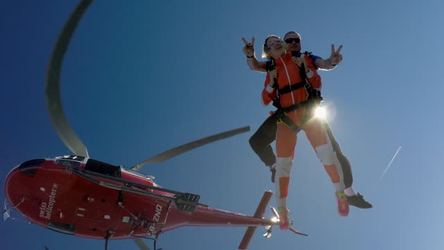 Skydivers jump out of helicopter over Alps