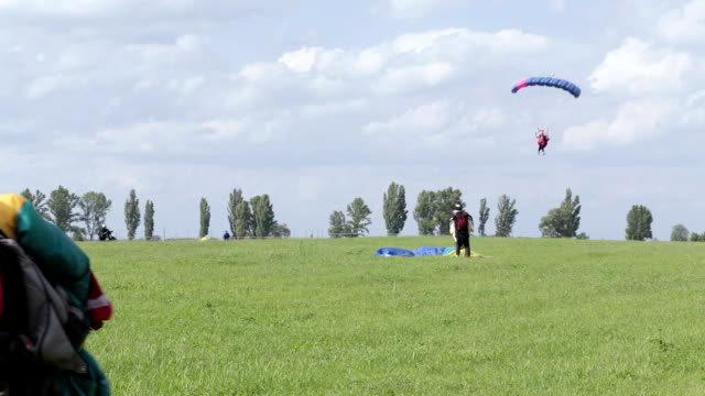 skydivers land on the field. an elderly skydiver carries his parachute. - landing touching down stock videos & royalty-free footage