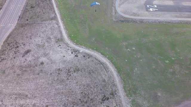 Skydivers landing in field