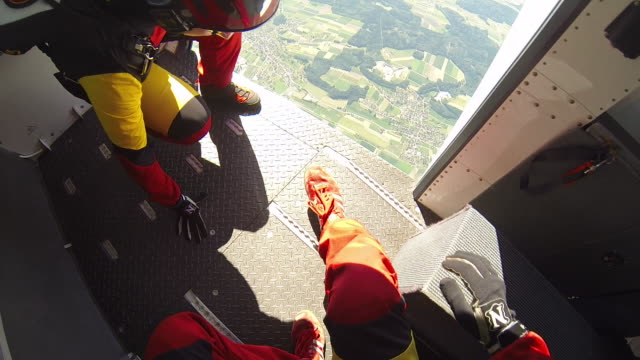 skydivers leap from airplane towards distant fields - imbracatura di sicurezza video stock e b–roll