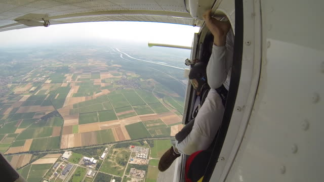 vidéos et rushes de skydivers leap from airplane towards distant fields - parachute