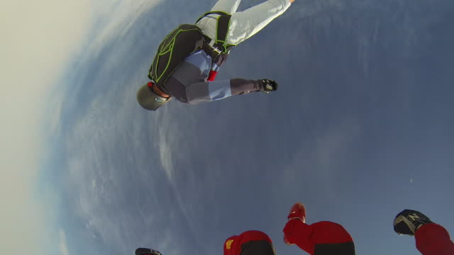 vídeos de stock e filmes b-roll de skydivers leap from airplane towards distant fields - câmara vestível