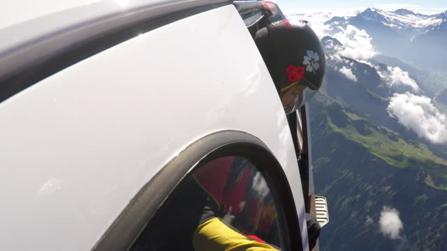 skydivers open helicopter door to jump over alps - skydiving stock videos & royalty-free footage
