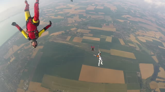Skydivers perform mid air stunts while falling towards ground