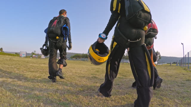 Skydivers walking across the airport field