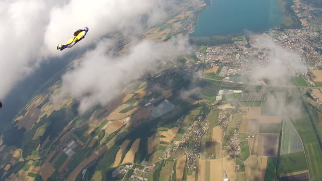 pov skydiving flying in formation with wingsuit skydivers through small clouds - exhilaration stock videos and b-roll footage