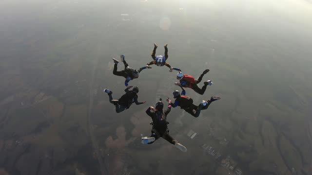 vidéos et rushes de skydiving group circle with pink smoke - parachute