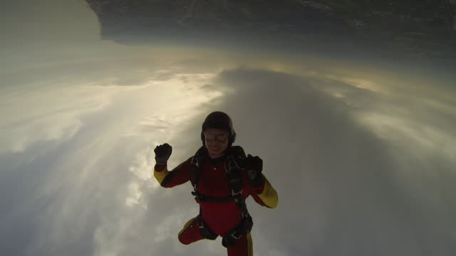 POV skydiving holding hands under a cloudy sky doing tricks with a smiling woman