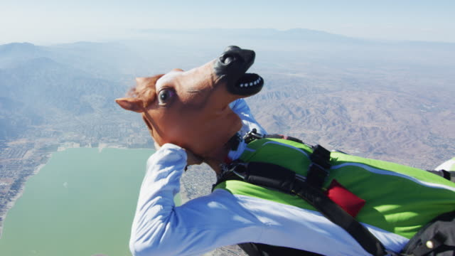 vídeos de stock e filmes b-roll de skydiving in a horse mask - esquisito