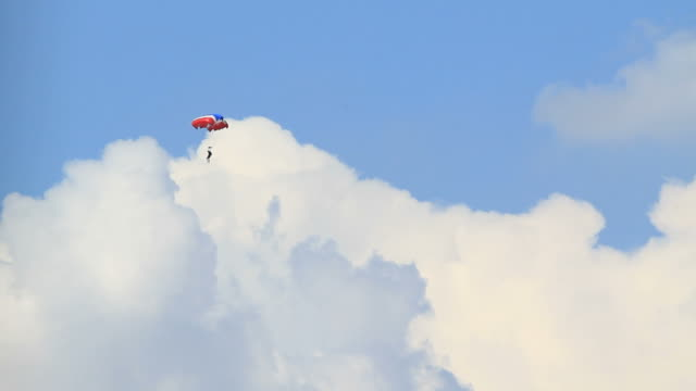 Skydiving in blue sky with clouds.