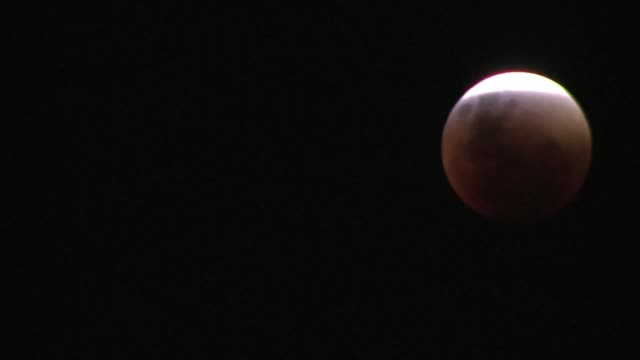 Skygazers are treated to a rare astronomical event when a swollen supermoon and lunar eclipse combine for the first time in decades showing the...