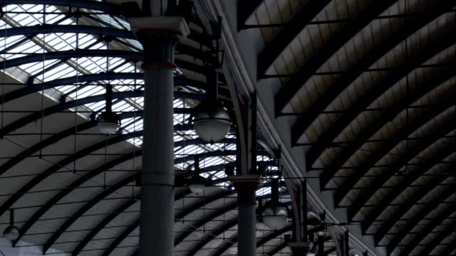 vídeos de stock e filmes b-roll de a skylight, arched beams, and columns make up the ceiling at newcastle central station in newcastle, england. available in hd. - claraboia