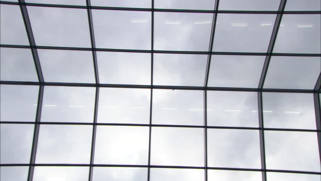 vídeos de stock e filmes b-roll de skylights frame a cloudy sky. - claraboia