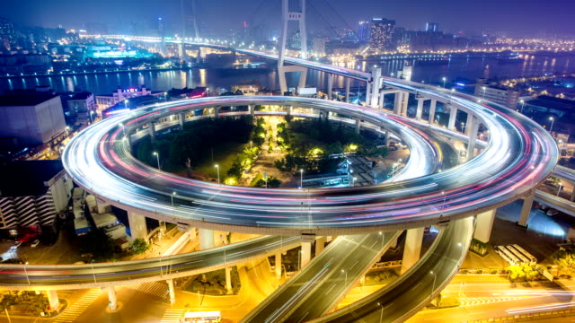 skyline and busy traffic on elevated road intersection at night, time lapse. - roundabout stock videos and b-roll footage