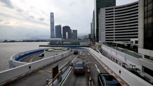 skyline and cars leaving parking lot in hong kong, real time.