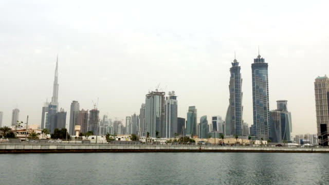 skyline and construction sites on waterfront in dubai, panning shot - architectural feature stock videos & royalty-free footage