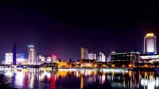 stockvideo's en b-roll-footage met skyline and illuminated buildings of ningbo at riverbank in the night.hyper lapse. - ningbo
