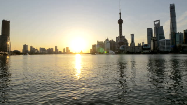 Skyline and modern buildings of shanghai at riverbank during sunset.