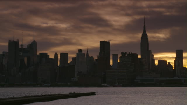 NYC skyline early morning.  The clouds are a pearl color with a touch of gold.  An old pier juts out into the water of the Hudson River, The Empire States building is featured.