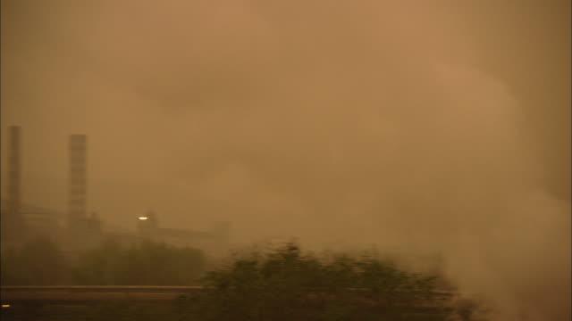ws ha pan skyline of apartment buildings and factory smokestacks in fog, beijing, china - スモッグ点の映像素材/bロール