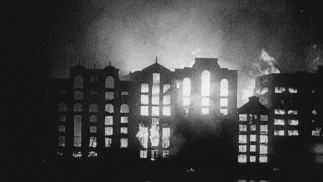 1942 MONTAGE Skyline of buildings engulfed in flames / Bristol, England, United Kingdom