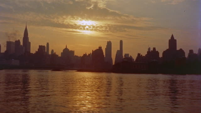 stockvideo's en b-roll-footage met 1956 ws skyline of midtown manhattan in silhouette with east river and roosevelt island in foreground / new york city - 1956