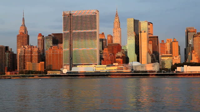 vídeos de stock e filmes b-roll de skyline of midtown manhattan seen from the east river showing the chrysler building and the united nations building, new york, united states of america - prédio chrysler
