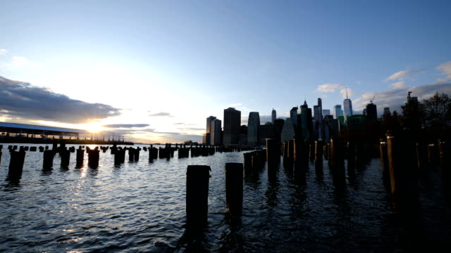 skyline of new york city from brooklyn bridge park at sunset - river east stock videos & royalty-free footage