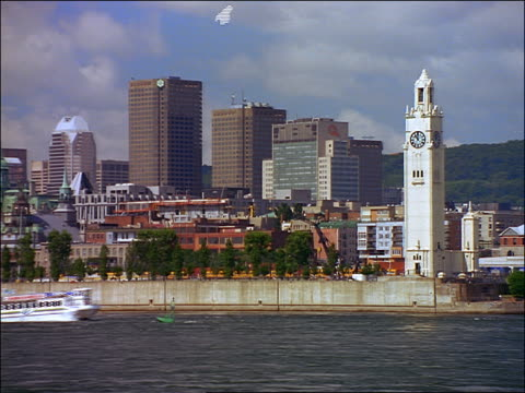 Skyline of Old Montreal with Victoria Pier Clock Tower + boat passing on river in foreground